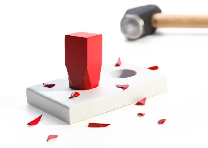 A square red peg hammered into a round hole surrounded by small pieces of the peg. Hammer in background. On a white background. Selective focus. Metaphor for a misfit, incompatibility.